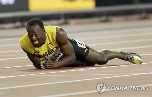 ▲ (런던 AP=연합뉴스) 우사인 볼트가 13일(한국시간) 영국 런던 스타디움에서 열린 남자 400m계주 결승에서 자메이카 마지막 주자로 나서 왼 다리 통증으로 트랙 위로 쓰러진 뒤 결승선을 통과하는 다른 나라 선수들을 바라보고 있다.