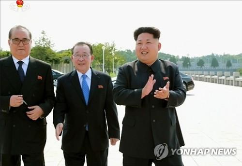 ▲ (서울=연합뉴스) 김정은 국방위원회 제1위원장이 '대사회의'에 참석한 북한 외교관들과 함께 기념사진을 찍었다고 15일 조선중앙통신이 보도했다. 최근 해외 주재 북한 중간 간부들의 동요가 커지고 있는 가운데 김정은 제1위원장이 이례적으로 이들을 만나 사진을 찍으며 '군기 잡기'에 나선 것이라는 분석이 나온다. 사진은 박수를 치는 김정은 제1위원장과 리수용 외무상(왼쪽), 김계관 외무성 제1부상(가운데)의 모습을 조선중앙TV 화면에서 캡처한 것. 2015.7.15